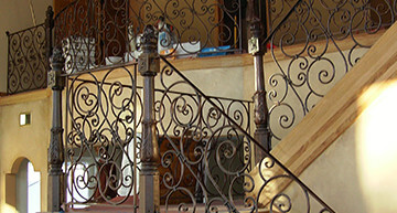 Elaborate custom wrought iron stair railing with fancy scroll balusters in a copper powder coated finish