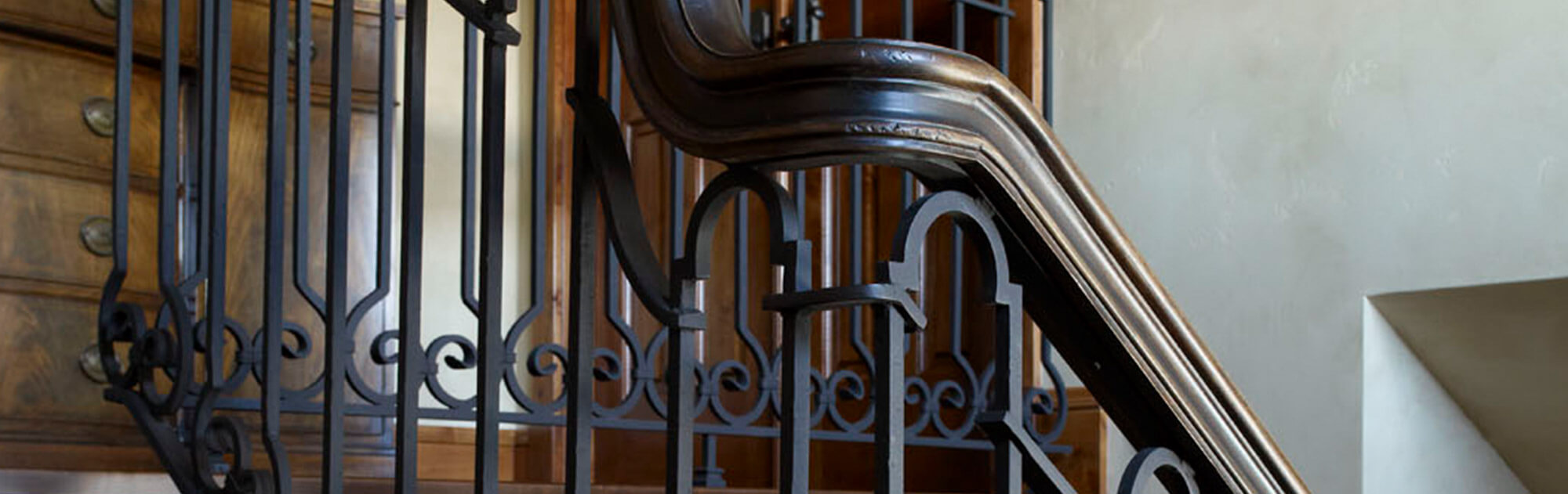 Close up of a custom stair railing with wood accents and black wrought iron scroll balusters